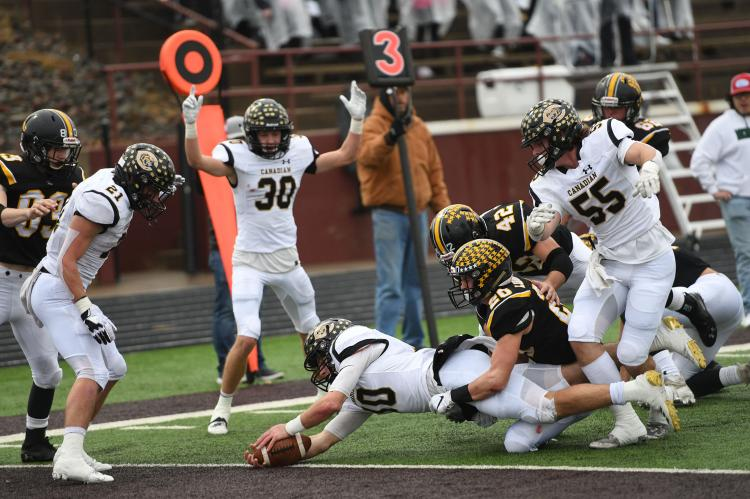 Wildcat Quarterback Grant McCook (10) dives for the goalline—one of 18 for the season—as teammate Bill Koetting (30) signals the touchdown and teammates Hayes Hufstedler (21) and Rhett Pennington (55) look on.