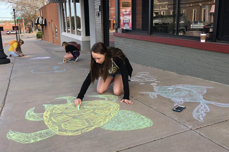 Clara Pulliam and friends create chalk art in front of Brown Bag Roasters Thursday