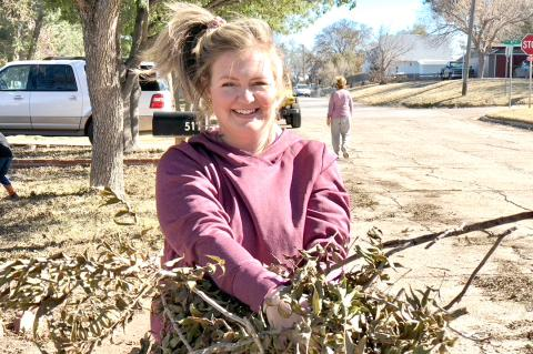 Church of Christ secretary Darcey Whitson pauses and smiles for a photo while cleaning up limbs.