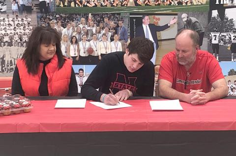 Coach Jay McCook and wife Lynn look on with pride as their son, Grant, signs a letter of intent with Northwestern Oklahoma State University.