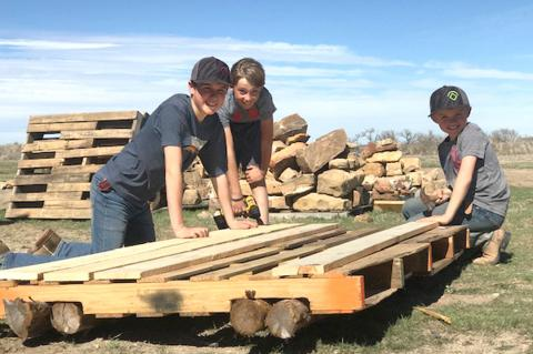Ben Bussard, Bridger and Parker Burrus construct a homemade raft, and float it down Wolf Creek