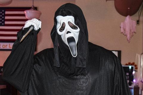 "Palace Theatre employee Gage Gerhardt as Ghostface from the movie ""Scream"" greats moviegoers on Saturday"
