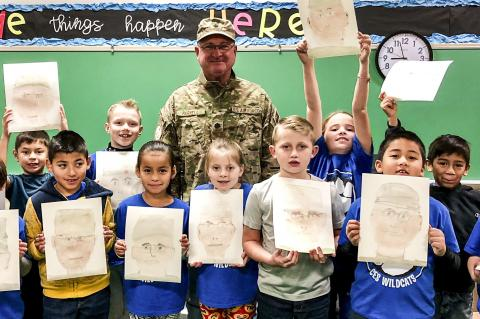 Veteran David Parnell poses with his portraits from Esmeralda Shields' second graders.