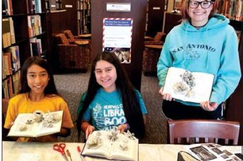 Hemphill County Librarian April Dillon taught a trio of teenagers how to make flowers out of old books during a recent Summer Reading program. Showing their creations are (l-r) Perla Vigil, Emely Perez, and Ashlyn Phillips.