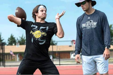 Grant McCook passing under close supervision from the staff during throwing drills. HALE HUGHES PHOTO